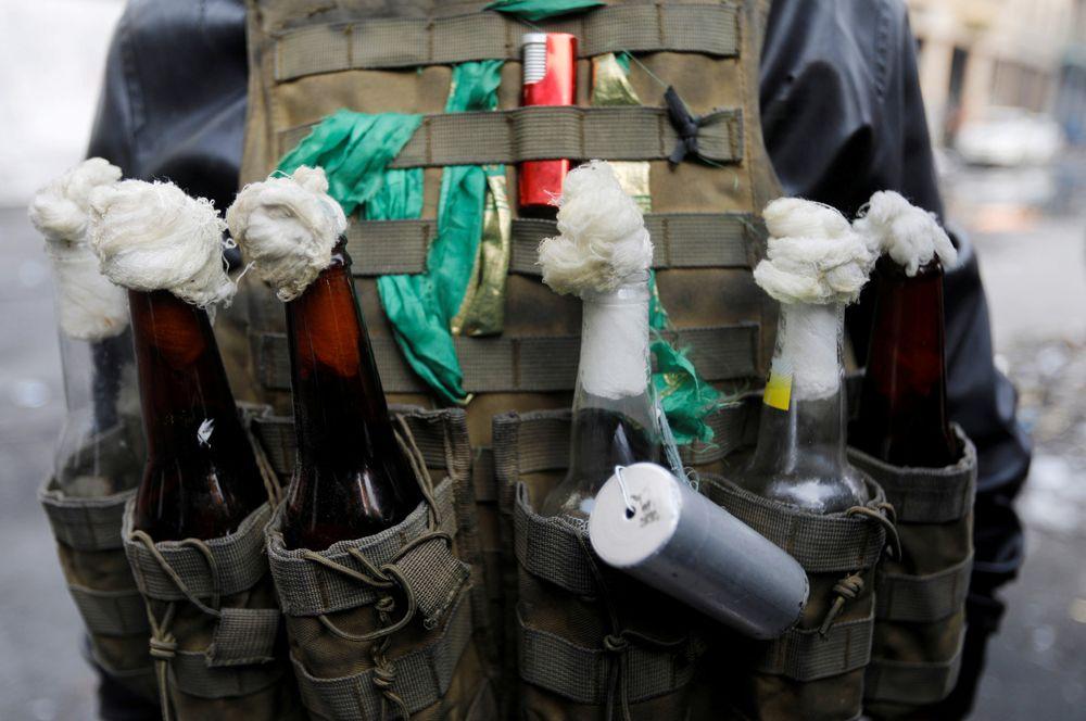 Демонстрант, вооруженный коктейлями Молотова, во время антиправительственных демонстраций в Багдаде, Ирак.