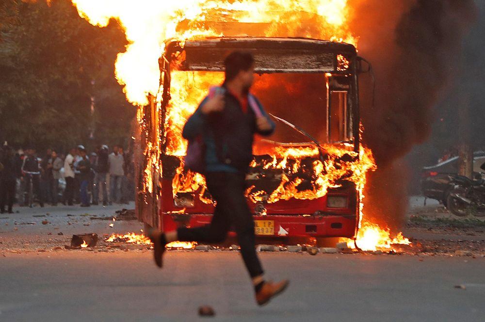 Автобус, который был подожжен демонстрантами во время протестов против нового закона о гражданстве в Нью-Дели.