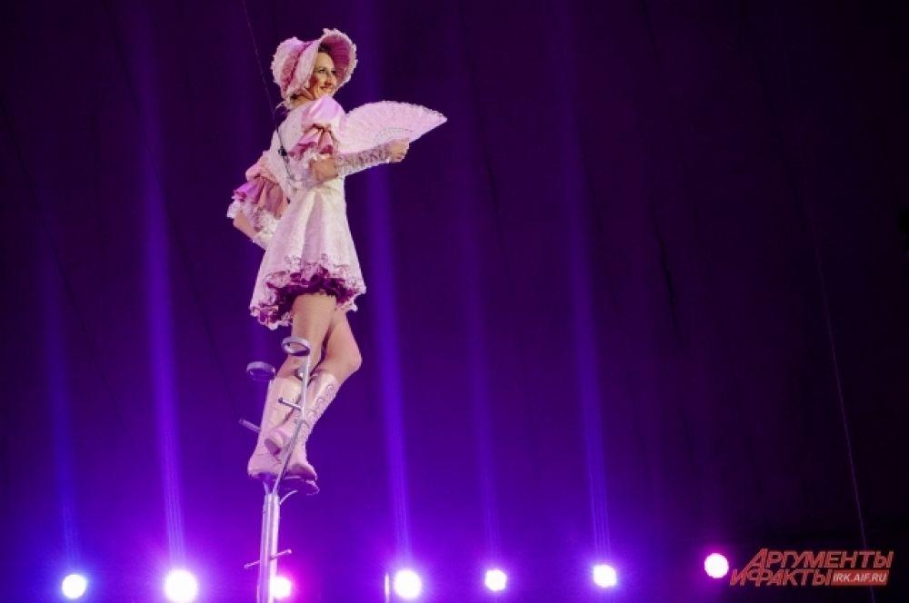 Глядя на непринуждённую позу девушки не скажешь, что она стоит на десятиметровой высоте, и единственная её опора - длинный цирковой шест, называемый першем
