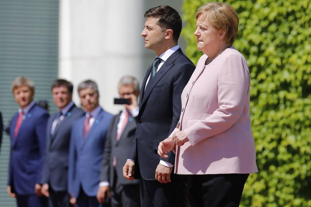 Канцлер Германии Ангела Меркель и президент Украины Владимир Зеленский во встречи в Берлине. Во время исполнения гимнов двух стран Меркель испытала приступ сильной дрожи. Это случилось с ней во второй раз, однако канцлер заверила журналистов, что с ней все в порядке. Недомогание, по ее словам, было вызвано обезвоживанием: в тот день в Берлине было аномально жарко.
