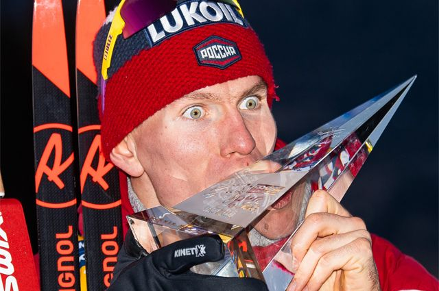 Александр Большунов целует приз после победы в массовом старте на 10 км во время «Тур де Ски».