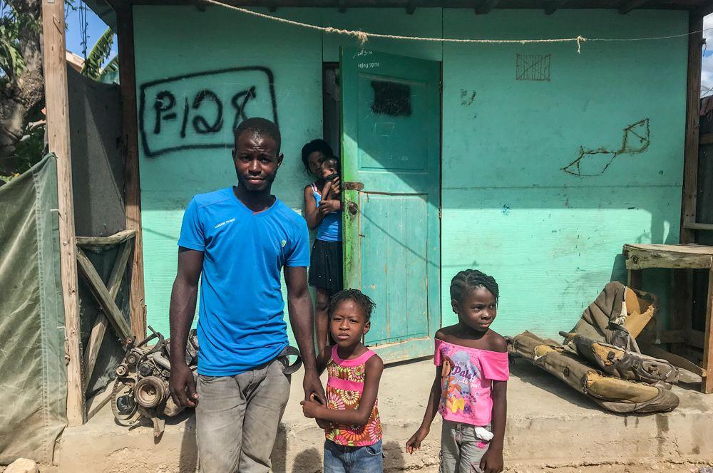 Семья перед своим домом в общине Ханаан на окраине Порт-о-Пренса. Ханаан был создан после землетрясения, сегодня там живет около 300 тысяч человек.