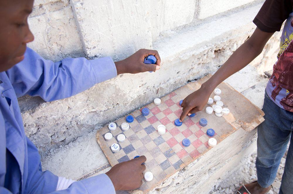 Дети играют в шашки пластиковыми крышками для бутылок.