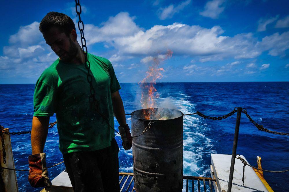 Член экипажа сжигает мусор.