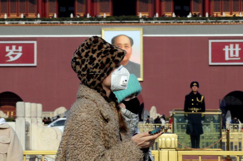 Туристы в масках на площади Тяньаньмэнь в Пекине.