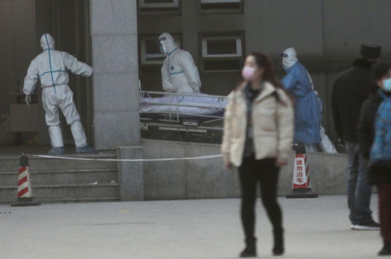 Медицинский персонал перевозит пациента из машины скорой помощи в больницу Цзиньинтань в Ухане, где осуществляется лечение пациентов с пневмонией, вызванной новым штаммом коронавируса.