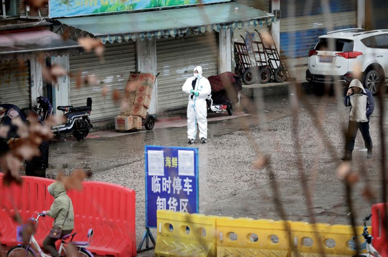 Человек в защитном костюме на закрытом для посещений рынке морепродуктов в Ухане.