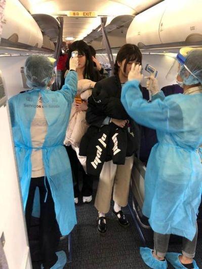 Медики измеряют температуру пассажиров на борту рейса Air China из Уханя в Макао.
