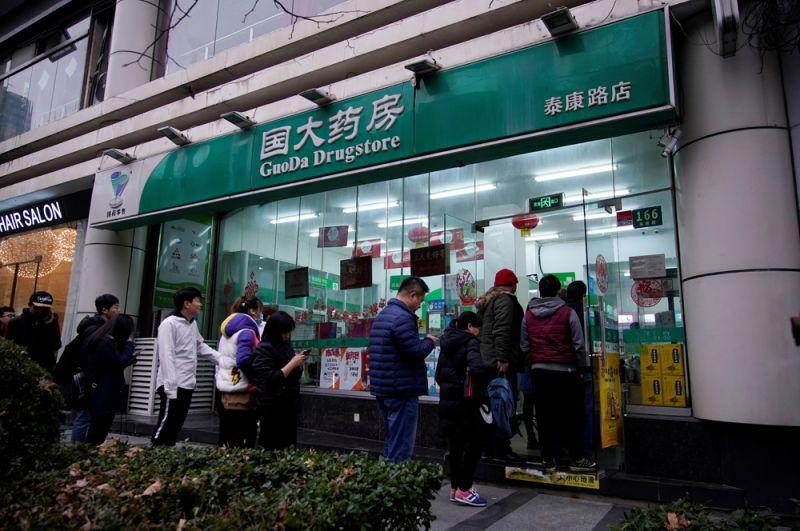 Люди стоят в очереди возле аптеки, чтобы купить медицинские маски в Шанхае.