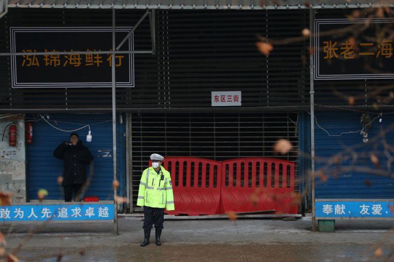 Полицейский в маске перед закрытым рынком морепродуктов в Ухане.