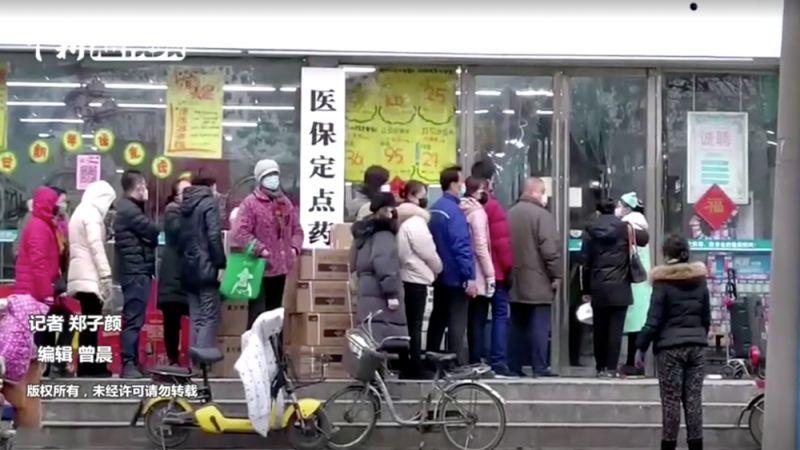 Жители Уханя стоят в очереди в магазин.
