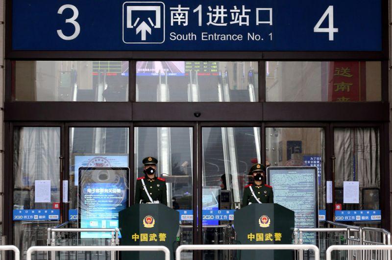 Сотрудники полиции в масках у входа в закрытый железнодорожный вокзал Ханькоу.