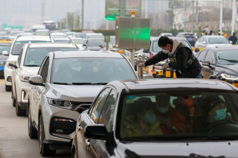 Проверка температуры у пассажиров в автомобиле на пропускном пункте в Ухане.
