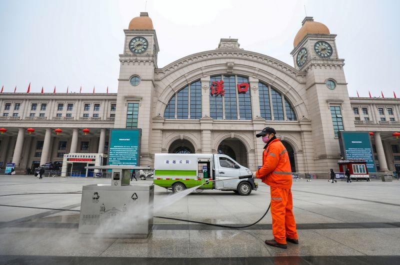 Рабочий дезинфицирует площадь перед закрытым железнодорожным вокзалом Ханькоу в Ухане.