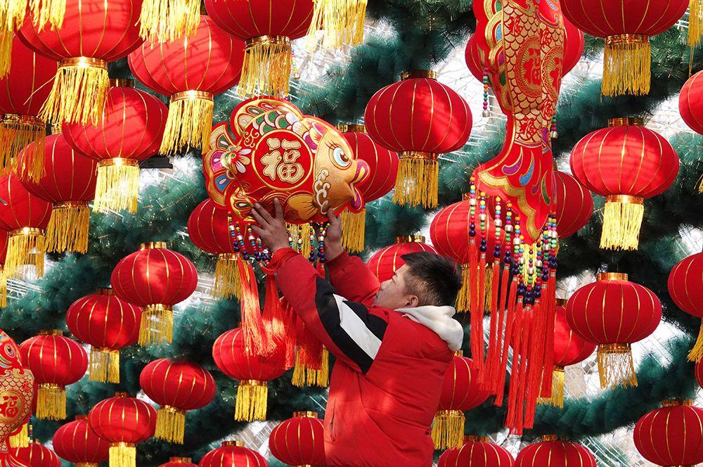 Мужчина развешивает традиционные красные фонари в парке перед празднованием Нового года в Пекине, Китай.