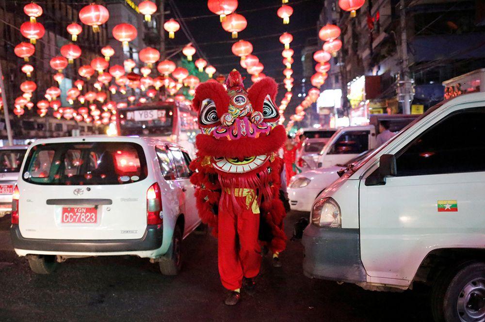 Артисты в костюмах львов приветствуют людей на улицах Янгона, Мьянма.
