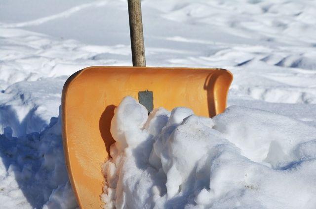 Девушка счищала широкой лопатой снег с тротуара рядом с автозаправочной станцией.