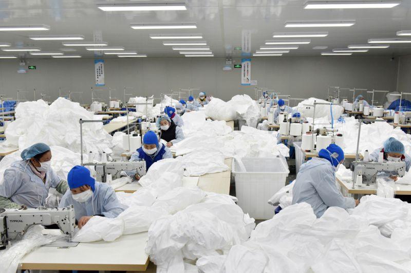 Рабочие шьют защитные костюмы на фабрике в Чаоху в провинции Аньхой.