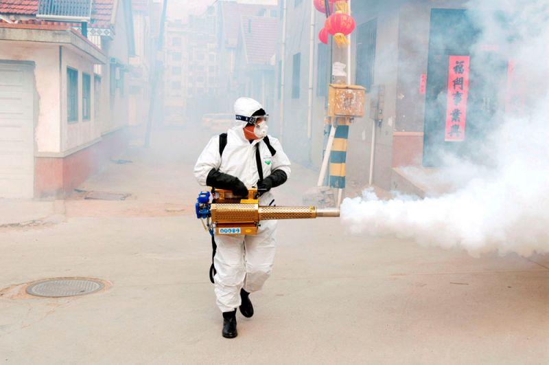 Рабочий в защитном костюме дезинфицирует улицы деревни около Циндао, провинция Шаньдун, Китай.