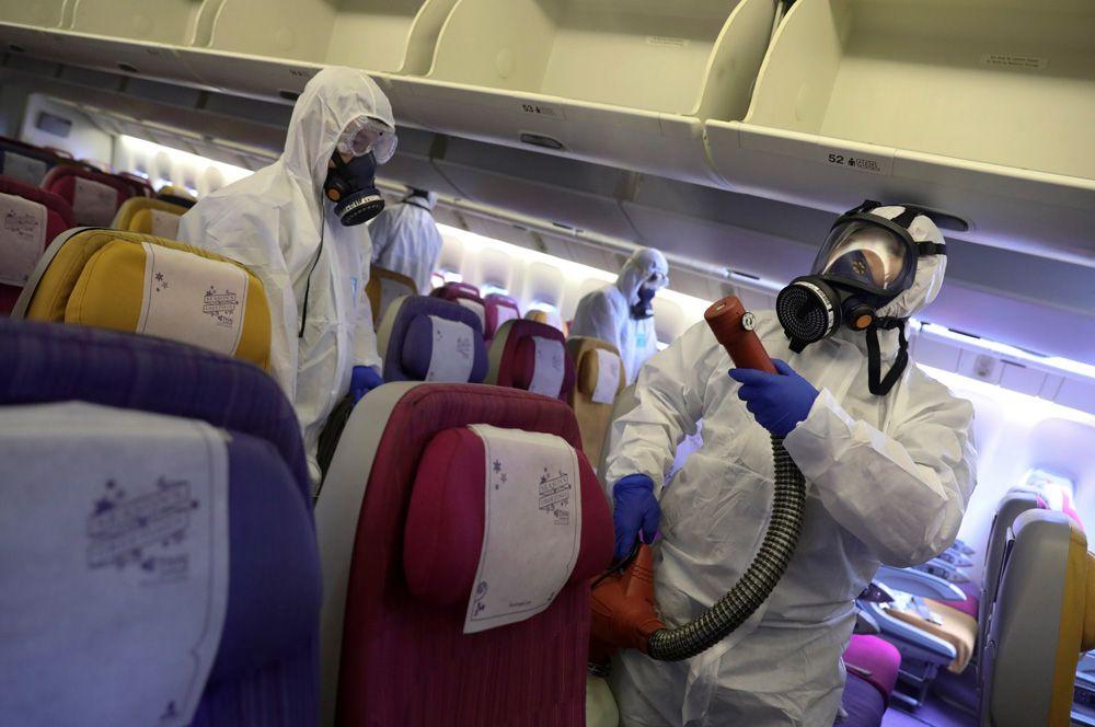 Члены экипажа Thai Airways дезинфицируют кабину самолета, чтобы предотвратить распространение коронавируса, в международном аэропорту Суварнабхуми в Бангкоке.
