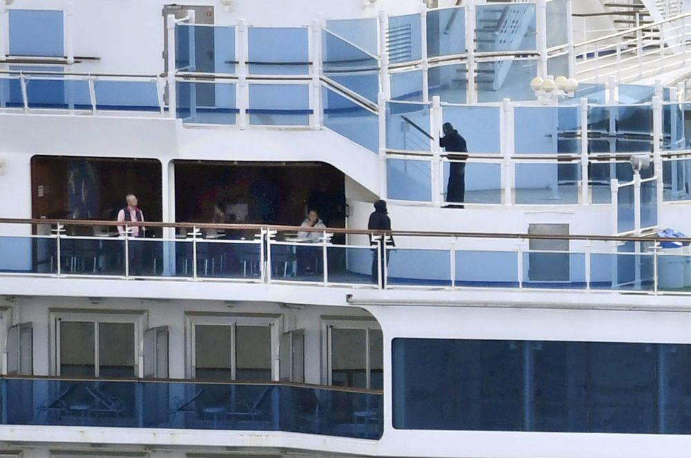 Пассажиры на борту круизного лайнера Diamond Princess, стоящего на рейду у порта Йокогамы.
