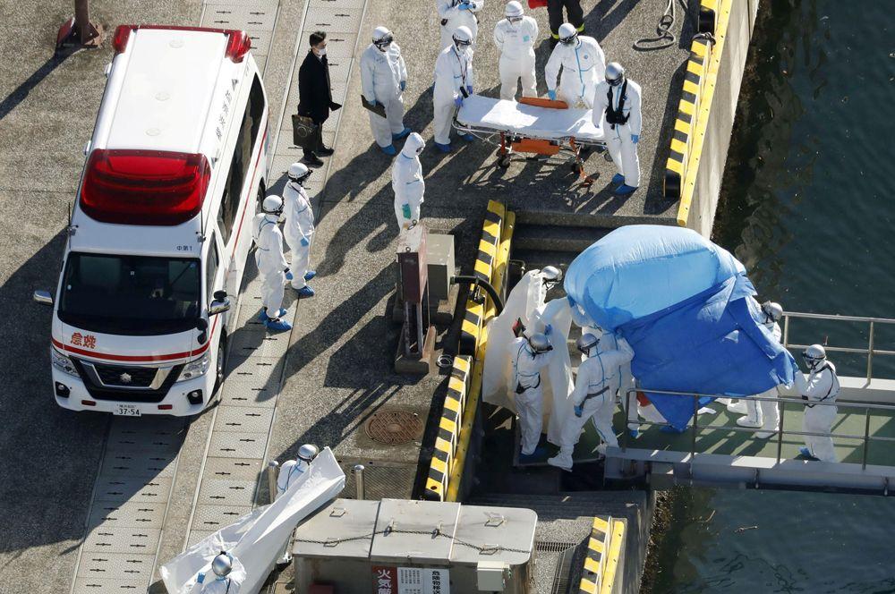 Работники скорой помощи госпитализируют заболевшего коронавирусом с лайнера Diamond Princess.