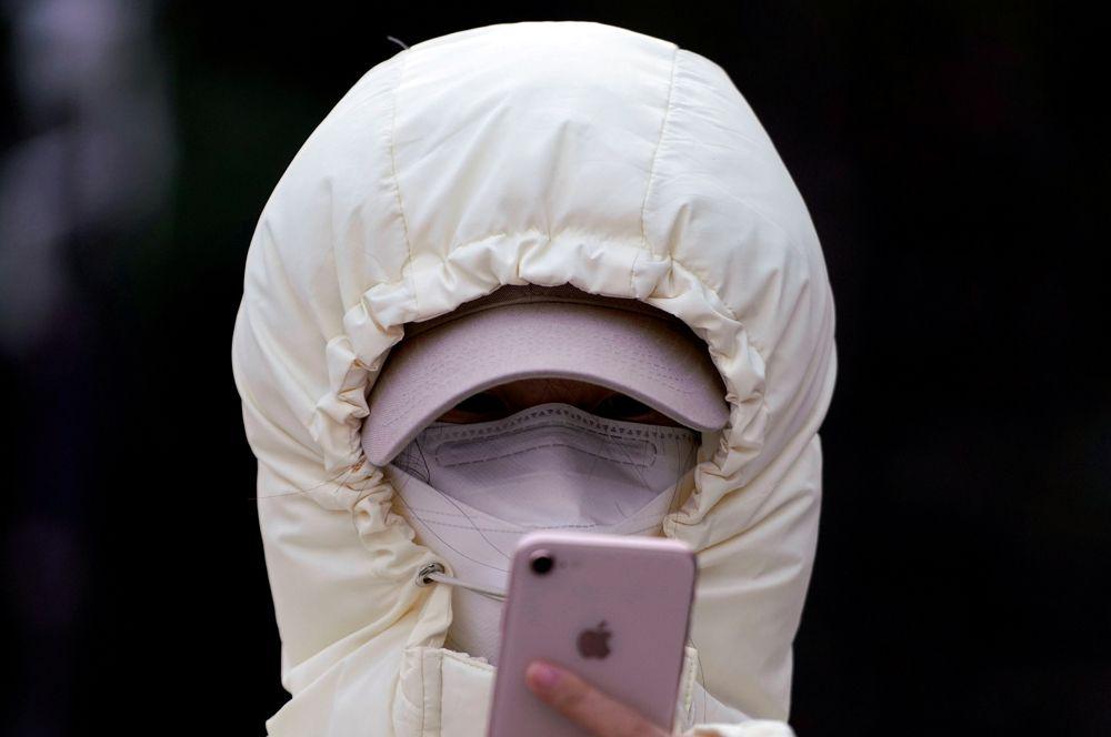 Женщина проверяет свой мобильный телефон, Шанхай.