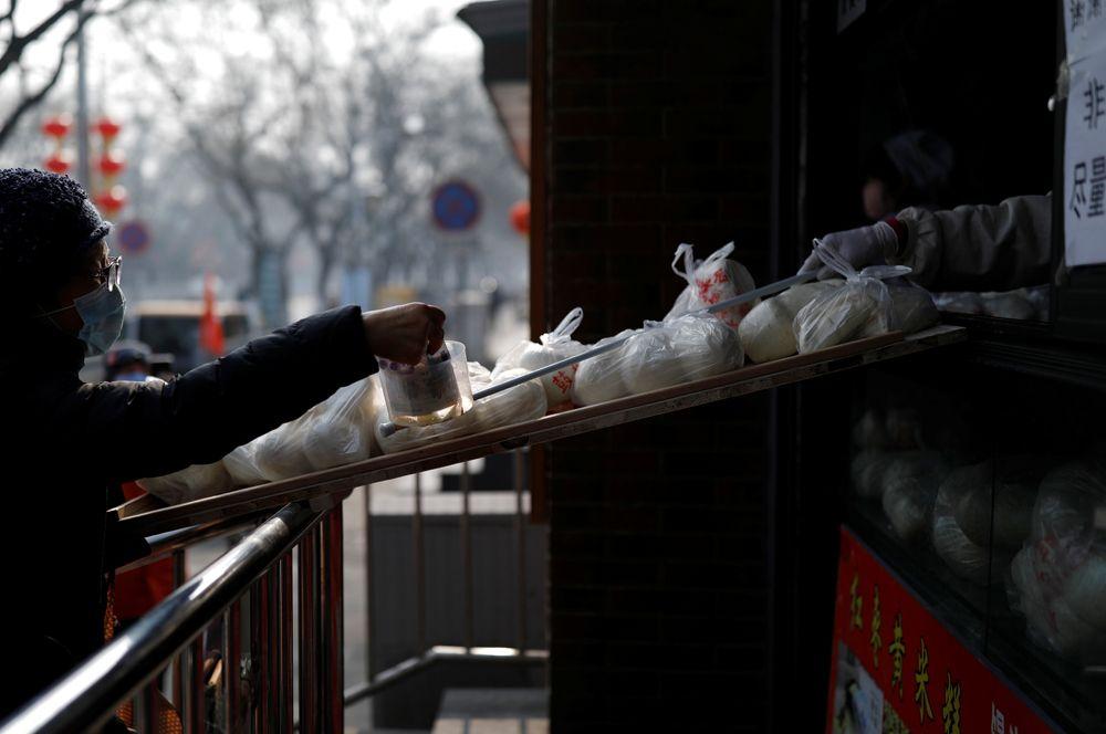 Покупатель в магазине, Пекин. В магазинах устанавливают специальные приспособления, чтобы покупатели меньше контактировали с продавцом и продуктами.