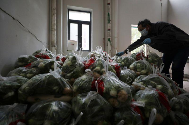 Социальный работник сортирует бесплатные овощи для владельцев домов в жилом комплексе.