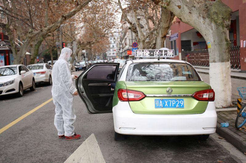 Водитель такси открывает дверь для пассажира.