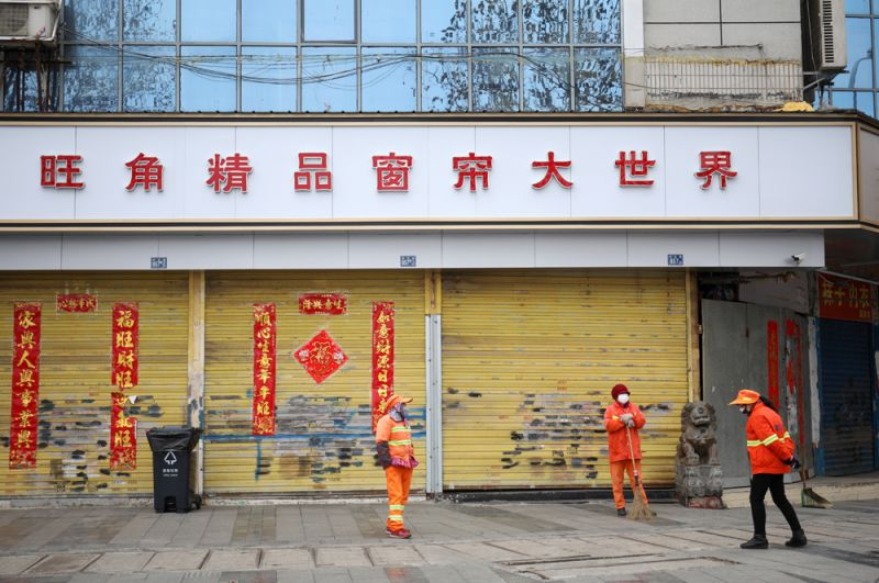 Уборщики в масках у закрытого магазина.