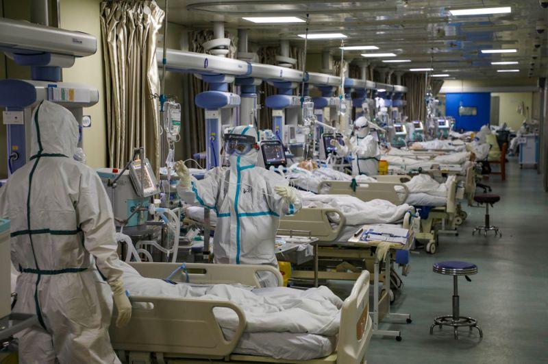 Медицинские работники в защитных костюмах обслуживают новых пациентов с коронавирусом в отделении интенсивной терапии специализированной больницы в Ухане.