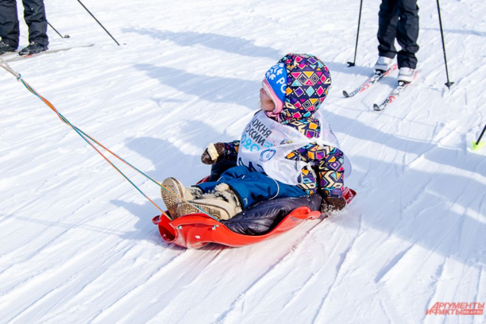 А кто-то, кто пока не может сам стоять на лыжах, с комфортом катился вслед за спортивными родственниками