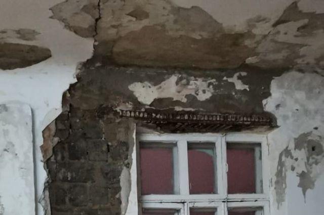 От стены школы у окна отпала штукатурка, виднеется кирпичная кладка.