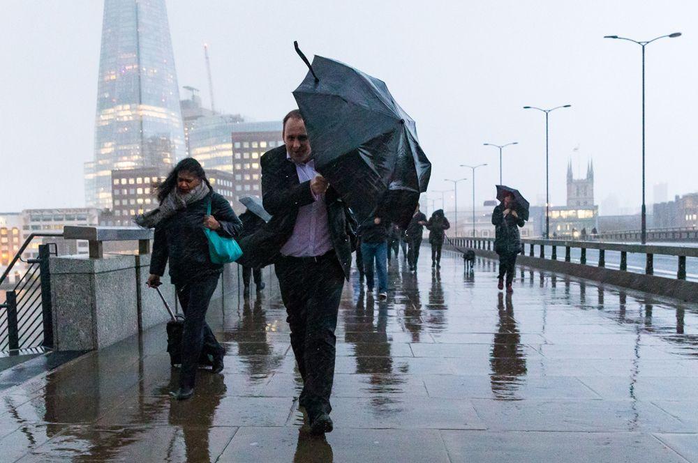 Пешеходы на Лондонском мосту во время проливного дождя с ветром.