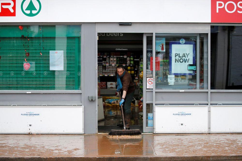 Мужчина очищает от воды и грязи вход в супермаркет в Тенбери Уэлс.