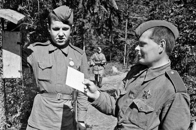 1943 год. Калининский фронт. Разведчики рядовые В.Ф. Голенищев (справа) и Е.С. Кузнецов опускают письма в почтовый ящик у передового края. Фото В. Гребиева.