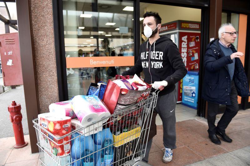 Мужчина в супермаркете в городе Казальпустерленго, который был закрыт из-за вспышки коронавируса.