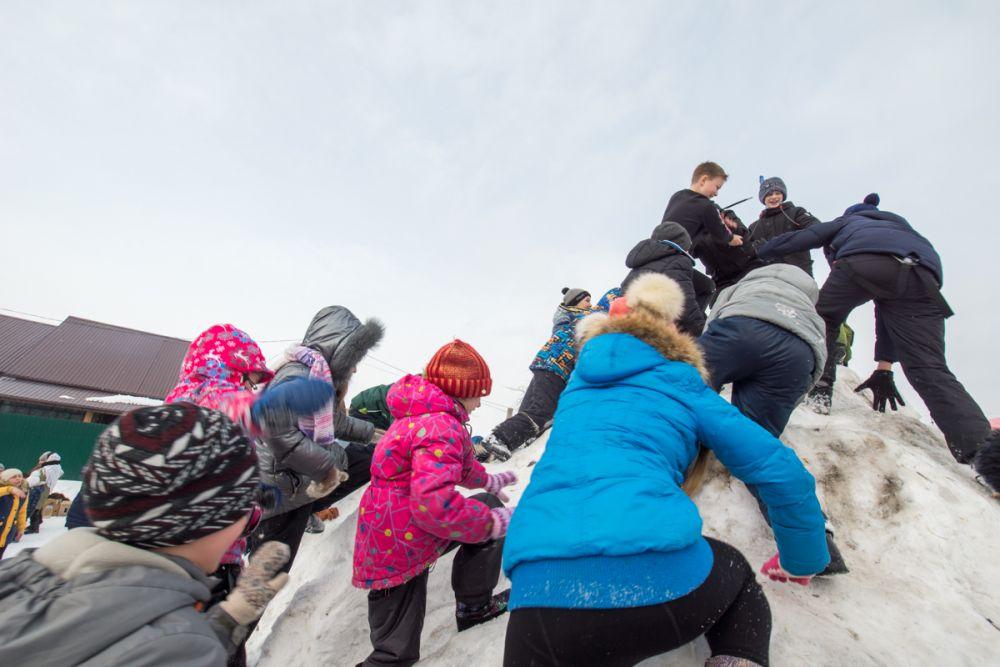 Дети с упоением штурмуют снежный городок.