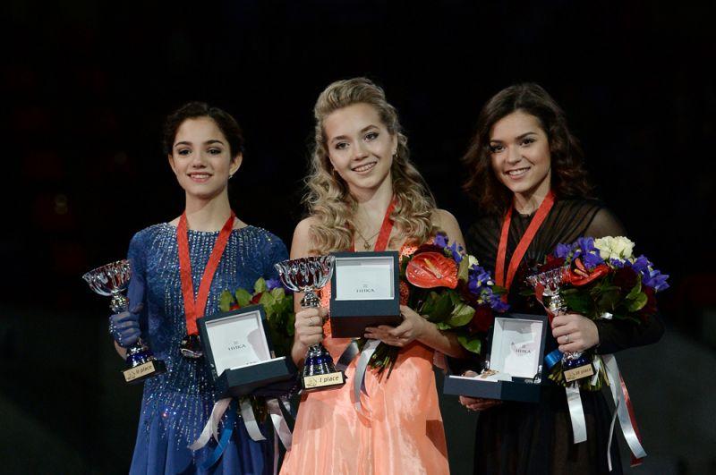 Призеры соревнований в женском одиночном катании на V этапе Гран-при по фигурному катанию в Москве во время церемонии награждения (слева направо): Евгения Медведева - 2-е место, Елена Радионова – 1-е место, Аделина Сотникова - 3-е место. 2015 год.