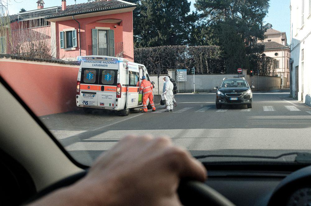 Медицинские работники у машины скорой помощи в Кодоньо, одном из городов, закрытых из-за вспышки коронавируса.