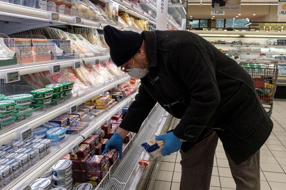 Мужчина совершает покупки в большом супермаркете в Кодоньо в Ломбардии.