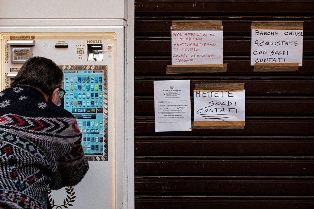 Мужчина в защитной маске покупает сигареты у табачного киоска самообслуживания, рядом — закрытая табачная лавка.
