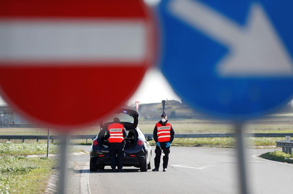 Карабинеры охраняют въезд в «красную зону» в Казальпустерленго в регионе Ломбардия.