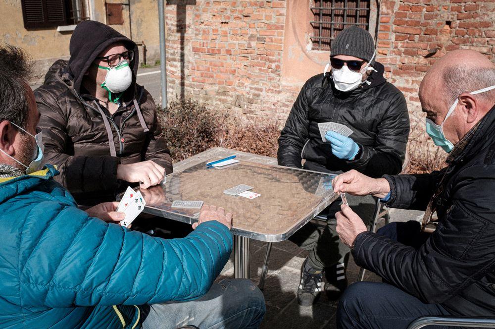 Местные жители в масках играют в карты на улице в Сан-Фьорано.