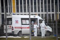Сотрудники скорой помощи надевают защитные костюмы на территории больничного комплекса в Коммунарке.