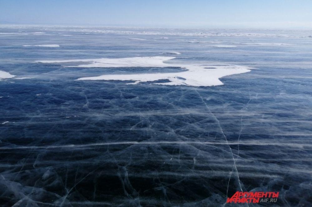 Зимняя гладь Байкала покрывает застывшую мощь озера.