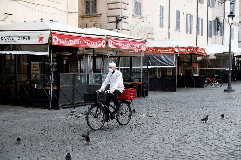 Сотрудник службы доставки еды на пустой Кампо деи Фиори в Риме.
