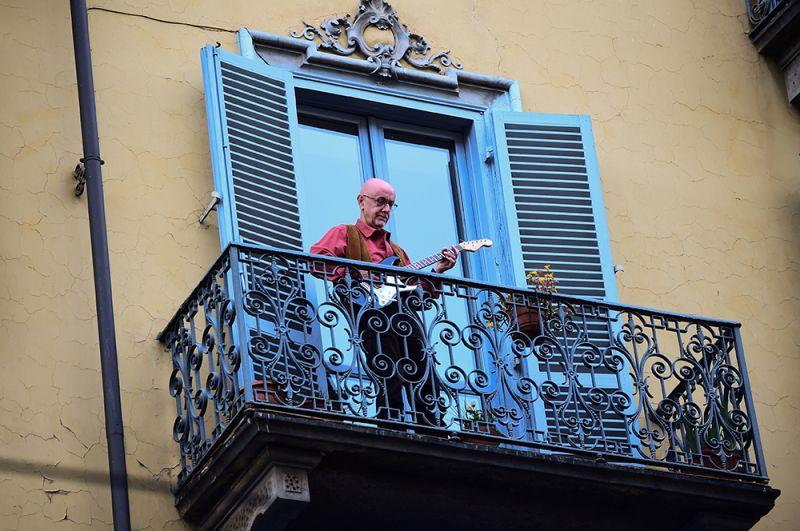 Мужчина играет на гитаре на своем балконе, Турин.