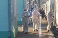 Сотрудники Роспотребнадзора проверяют пассажиров на вокзале в Смоленске в защитной одежде.
